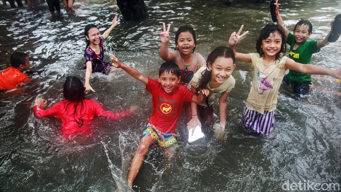Anak-anak bermain di banjir di Jl Kapten Tendean, Jakarta, Sabtu, (20/2/2021).