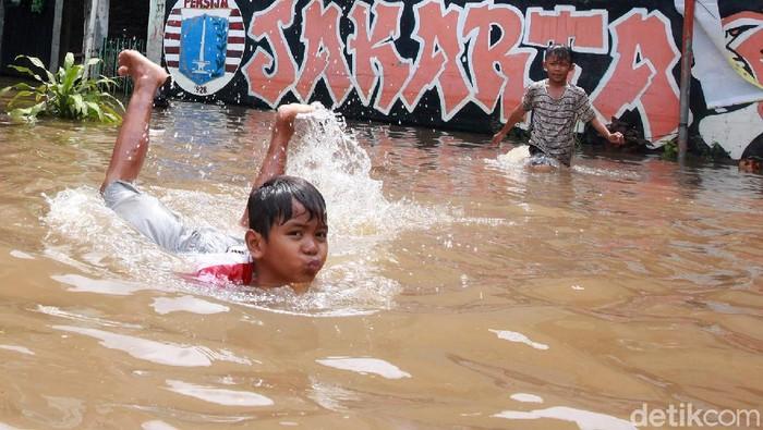 Banjir merendam salah satu RT di Ulujami, Jakarta Selatan, Sabtu (20/2/2021). Genangan banjir ini justru jadi arena bermain anak-anak.