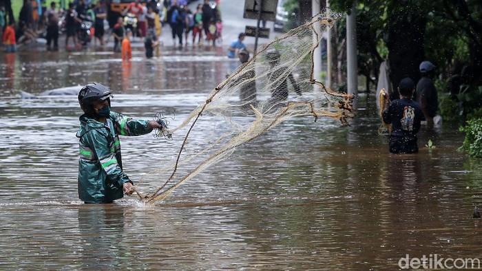 Jalan TB Simatupang, Jakarta Selatan, terendam banjir, Sabtu (20/2/2021) pagi. Kondisi ini dimanfaatkan sebagian warga untuk menjala ikan.
