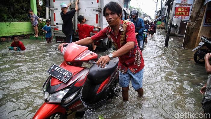 Sejumlah warga mendorong motornya yang mogok di kawasan yang terendam banjir, Kapuk Muara, Penjaringan, Jakarta Utara, Sabtu (20/2). Banyak motor warga yang mogok akibat nekat menerobos banjir setinggi 70 cm itu.