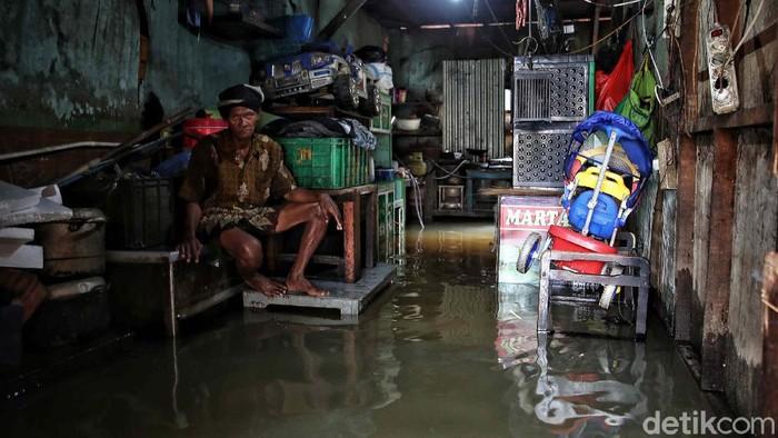Sejumlah warga melintas di kawasan jalan Kapuk Muara, Penjaringan, Jakarta Utara, Sabtu (20/2). Banjir yang mulai datang sejak Subuh tadi mulai mengenangi pemukiman setinggi 30-70 cm.
