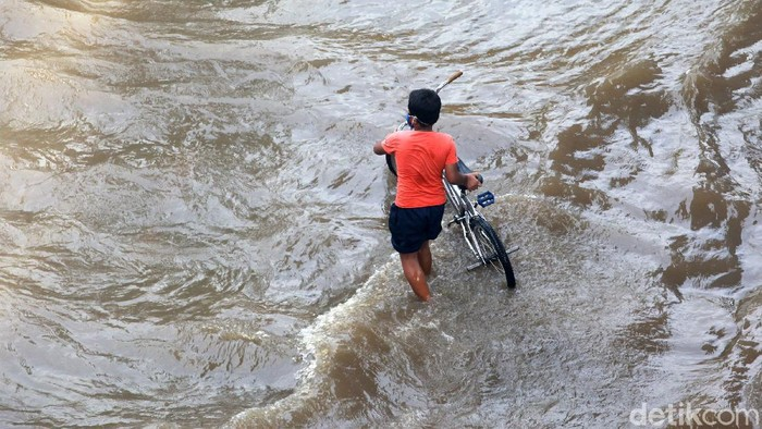 Pesepeda melintasi banjir di Jl Tendean, Sabtu, (20/2/2021). Sepeda tanpa mesin ini dijamin tidak mogok melewati ketinggian air.