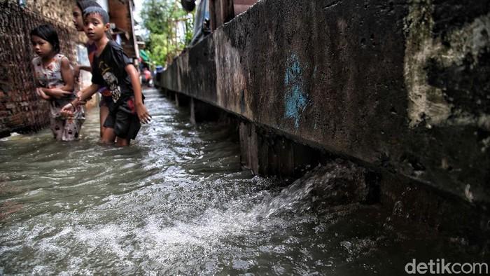 Sejumlah warga beraktivitas di kawasan tanggul sungai di RT 7 RW 4,Kapuk Muara, Penjaringan, Jakarta Utara, Sabtu (20/2). Banjir yang mengenangi kawasan pemukiman tersebut diakibatkan karena intensitas hujan yang tinggi sejak semalam dan tanggul yang bocor karena tidak terawat sehingga tidak mampu menahan laju luapan sungai Kapuk Muara dan menyebabkan banjir