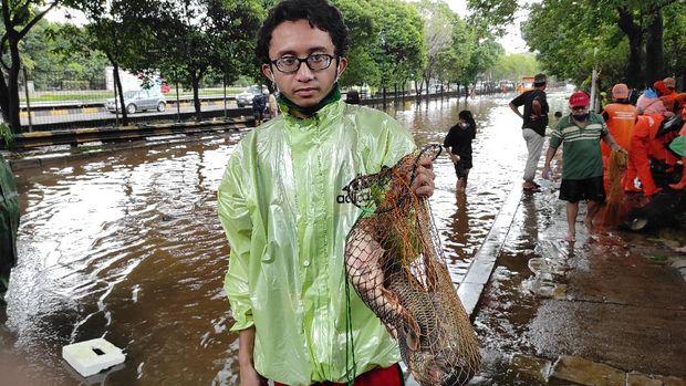 Warga sekitar Kementan menjaring ikan saat terjadi banjir.