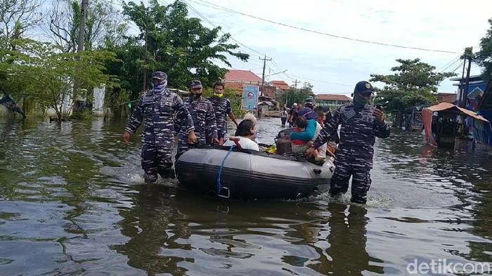 Anggota TNI AL mengevakuasi warga terdampak banjir di Panjang Baru, Pekalongan Utara, Kota Pekalongan, Minggu (21/2/2021).