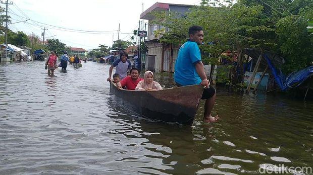 Banjir di Kota Pekalongan, Jawa Tengah, hingga saat ini belum surut, Minggu (21/2/2021). Perahu nelayan mondar-mandir di jalanan sebagai alat transportasi andalan warga terdampak.