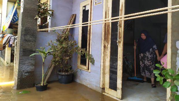 Warga Cipinang Melayu mulai membersihkan rumah dari sisa banjir, MInggu (21/2/2021).