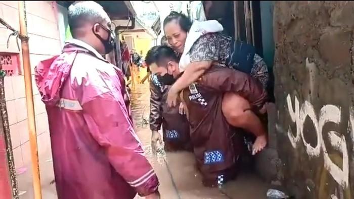 Kapolsek Cilandak Kompol Iskandarsyah menggendong warga yang sakit di lokasi banjir. Screenshot video diberikan Kabid Humas Polda Metro Jaya Kombes Yusri Yunus.