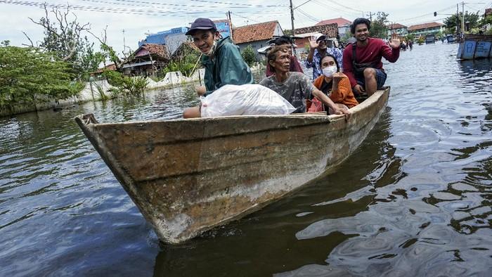 Warga pemilik kapal menarik perahu miliknya yang ditumpangi warga melewat banjir di Pekalongan, Jawa Tengah, Minggu (21/2/2021). Untuk mendapatkan penghasilan tambahan, sejumlah warga pemilik perahu memanfaatkan momentum banjir untuk menyewakan perahu miliknya untuk membuka jasa mengantar warga terdampak banjir melewati genangan air dengan biaya antara Rp5.000-Rp15.000 per orang di sepanjang Jalan Kusuma Bangsa dengan jarak sekitar dua kilometer. ANTARA FOTO/Harviyan Perdana Putra/foc.