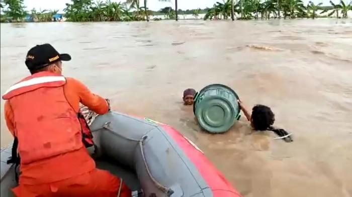 Petugas menyelamatkan dua korban banjir yang menerobos banjir menggunakan ember