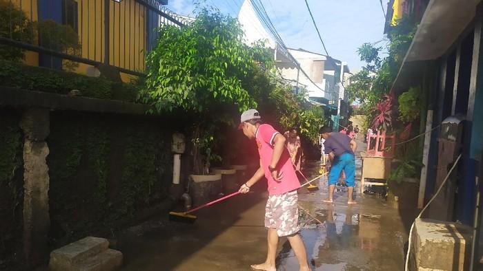 Warga Cipinang Melayu Bersih-bersih Lumpur Sisa Banjir