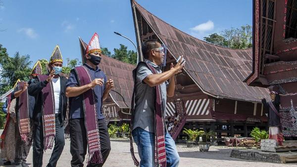 Wisatawan menari tarian tor tor di depan patung Sigale-gale di Desa Wisata Tomok, Simanindo, Samosir, Sumatera Utara, Minggu (21/2/2021).