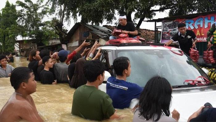Dedi Mulyadi Nekat Bawa Mobil Mewah Terobos Banjir. Ini ia lakukan untuk membagi-bagikan bantuan ke warga yang terdampak banjir.