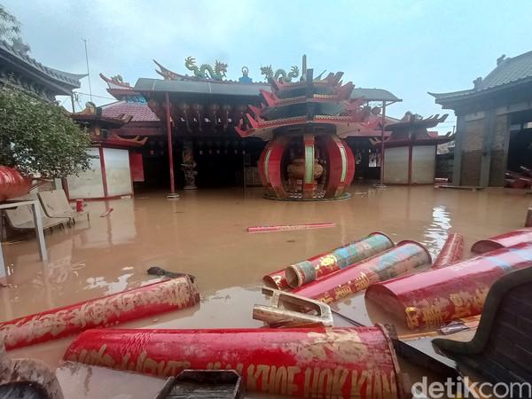 Tampak puluhan lilin berserakan akibat terjangan banjir luapan Sungai Citarum, dan Cibeet. Lilin kecil mengambang sebagian, dan yang besar tergelatak di gerbang pintu masuk kelentengnya.