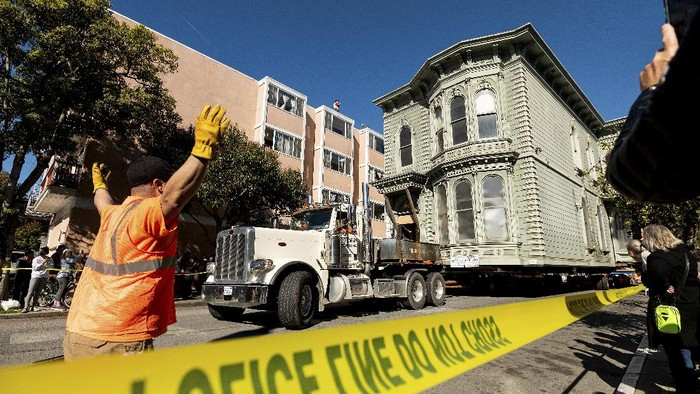 CORRECTS APPROXIMATE COST TO $400,000, INTEAD OF $200,000 - A truck pulls a Victorian home through San Francisco on Sunday, Feb. 21, 2021. The house, built in 1882, was moved to a new location about six blocks away to make room for a condominium development. According to the consultant overseeing the project, the move cost approximately $400,000 and involved removing street lights, parking meters, and utility lines. (AP Photo/Noah Berger)
