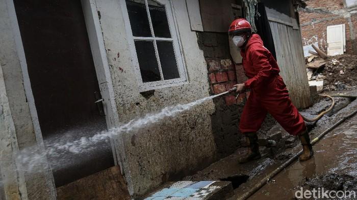 Petugas Pemadam Kebakaran membersihkan sisa lumpur pasca banjir di kawasan Tebet, Jakarta, Senin (22/2/2021).