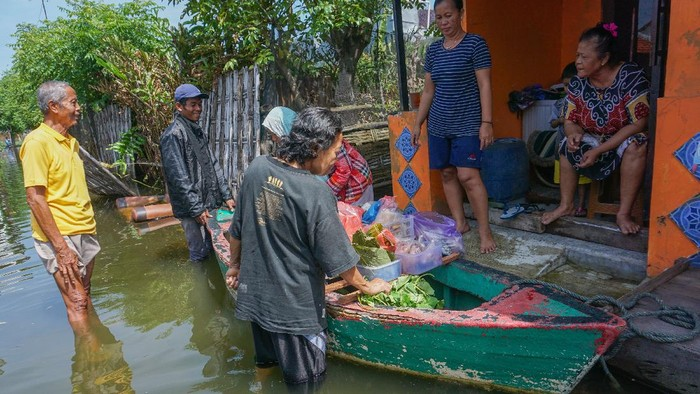 Warga terdampak banjir berbelanja di pedagang sayuran keliling yang menggunakan perahu di Pekalongan, Jawa Tengah, Senin (22/2/2021). Sejak banjir menggenangi Kota Pekalongan, pedagang berinisiatif berjualan menggunakan perahu untuk memudahkan akses melewati banjir. ANTARA FOTO/Harviyan Perdana Putra/rwa.