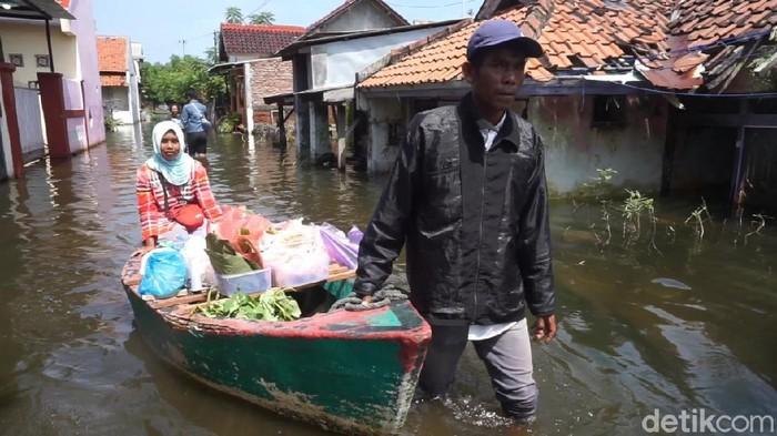 Penjual sayur di Kota Pekalongan jualan naik perahu di tengah banjir, Senin (22/2/2021).