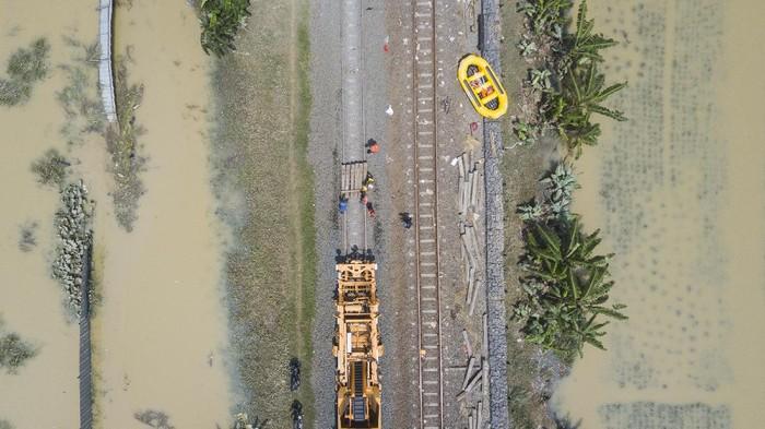 Petugas memperbaiki rel kereta api yang rusak akibat banjir di Kedungwaringin, Kabupaten Bekasi, Jawa Barat, Senin (22/2/2021). PT KAI membatalkan sementara perjalanan Kereta API (KA) jarak jauh dan KA lokal keberangkatan Daop 1 Jakarta karena adanya kerusakan pondasi batu pada rel karena tergerus air luapan banjir di Lemah Abang Km 55+100 sampai dengan Km 53+600. ANTARA FOTO/ Fakhri Hermansyah/aww.