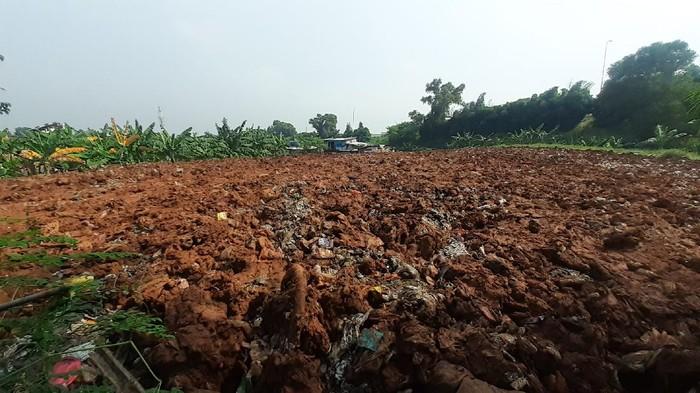 Sampah seluas lapangan sepak bola di Kampung Caman Kota Bekasi, ditutup dengan tanah merah.