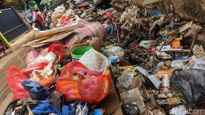 Sampah sisa banjir menumpuk di jalan Wijaya Timur, Petogogan, Jakarta Selatan. Begini potretnya.