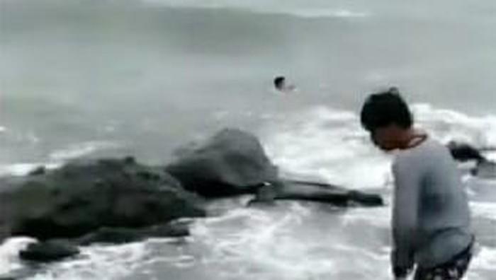 Tangkapan layar video viral 2 pria di Makassar terjun ke gelombang tinggi laut demi selamatkan bocah tenggelam (dok. Istimewa).