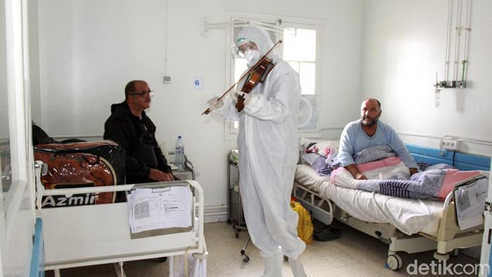 Dr. Mohamed Salah Siala plays the violin for patients on the COVID wards of the Hedi Chaker hospital in Sfax, eastern Tunisia, Saturday Feb. 20, 2021. When the 25-year-old decided to get out his violin one day at Hedi Chaker Hospital in city of Sfax and play, it won praise for boosting the morale of virus sufferers who remained isolated and needed a smile. (AP Photo)