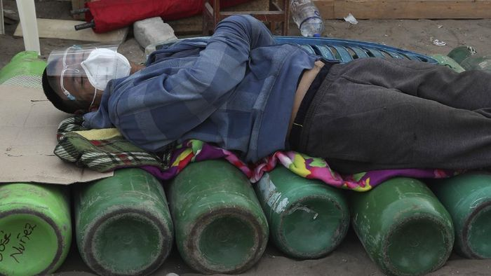 A youth rests on his empty oxygen cylinder waiting for a refill shop to open in the San Juan de Lurigancho neighborhood of Lima, Peru, Monday, Feb. 22, 2021, as the lack of medical oxygen to treat COVID-19 patients continues to be the norm nationwide. The shop can only refill about 40 tanks a day, triggering long lines outside private providers with many spending the night outside so as to not lose their place. (AP Photo/Martin Mejia)