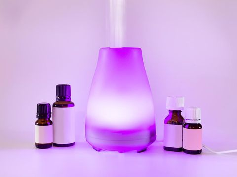 Aromatherapy essential oil diffuser with purple light and oil bottles