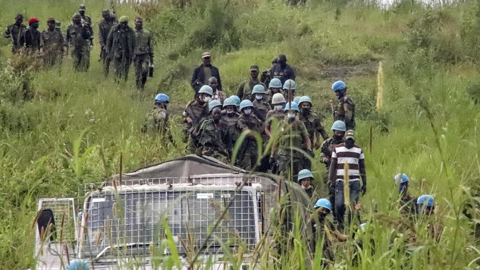 United Nations peacekeepers and Congolese forces guard an area leading to where bodies were found near to where a U.N. convoy was attacked and the Italian ambassador to Congo killed, in Nyiragongo, North Kivu province, Congo Monday, Feb. 22, 2021. The Italian ambassador to Congo Luca Attanasio, an Italian Carabineri police officer and their Congolese driver were killed Monday in an attack on a U.N. convoy in an area that is home to myriad rebel groups, the Foreign Ministry and local people said. (AP Photo/Justin Kabumba)
