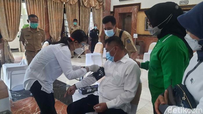 Vaksinasi COVID-19 tahap dua digelar hari ini di Surabaya. Petugas pelayanan publik, lansia hingga beberapa kepala OPD pemkot disuntik vaksin.