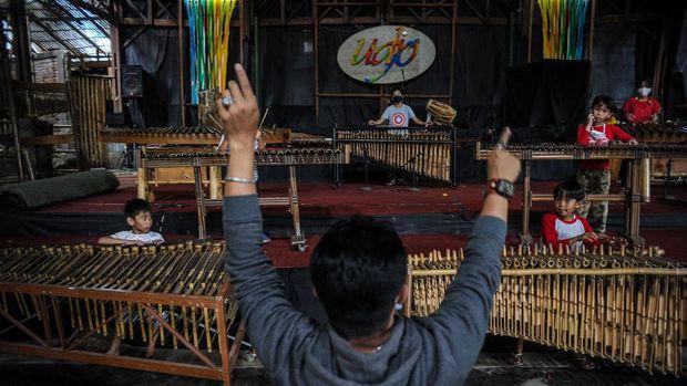 Seorang instruktur memegang angklung di aula pementasan yang kosong di Saung Angklung Udjo.
