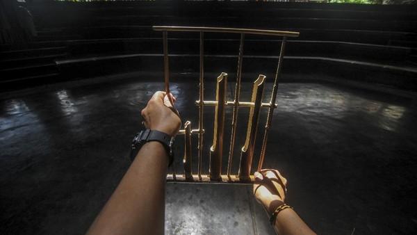 Seorang instruktur memegang angklung di aula pementasan yang kosong di Saung Angklung Udjo, Bandung.