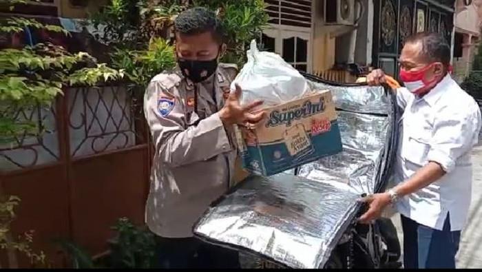 Anggota Bhabinkamtibmas Bripka Parmuji melakukan delivery isoman