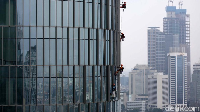 Pekerja membersihkan kaca gedung bertingkat di Jakarta, Selasa (23/2/2021). BPJS Ketenagakerjaan mengungkapkan kasus kecelakaan kerja di Indonesia menurun.