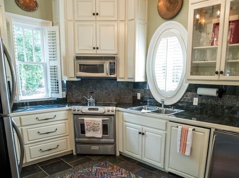small kitchen in a pool guest house with appliances and cabinets and a counter and custom lighting