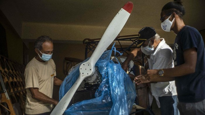 Adolfo Rivera gets out the wooden, two-seater plane he is building in the garage of his apartment building in Havana, Cuba, Friday, Feb. 19, 2021. Rivera, a 70-year-old mechanical engineer, and university professor has been making the wooden, two-seater aircraft for eight years now, with government permission and estimates he has spent about 5,500 Euros ($6,660). (AP Photo/Ramon Espinosa)