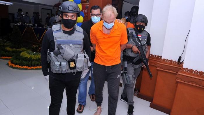 Dua orang warga negara Rusia Andrei Kovalenka alias Andrew Ayer (kedua kanan) dan Ekaterina Trubkina (kedua kiri) dihadirkan petugas saat rilis di Kantor Imigrasi Kelas I Khusus TPI Ngurah Rai, Badung, Bali, Rabu (24/2/2021). Andrei Kovalenka yang juga merupakan buronan Interpol tersebut bersama pasangannya Ekaterina Trubkina berhasil ditangkap di kawasan Seminyak, Bali, usai melarikan diri dari Kantor Imigrasi Ngurah Rai sejak Kamis (11/2) lalu saat proses administrasi pemindahannya ke Rumah Detensi Imigrasi Denpasar untuk menunggu pendeportasian setelah sebelumnya menjalani hukuman pidana di Lapas Kerobokan karena kasus narkotika. ANTARA FOTO/Fikri Yusuf/foc.