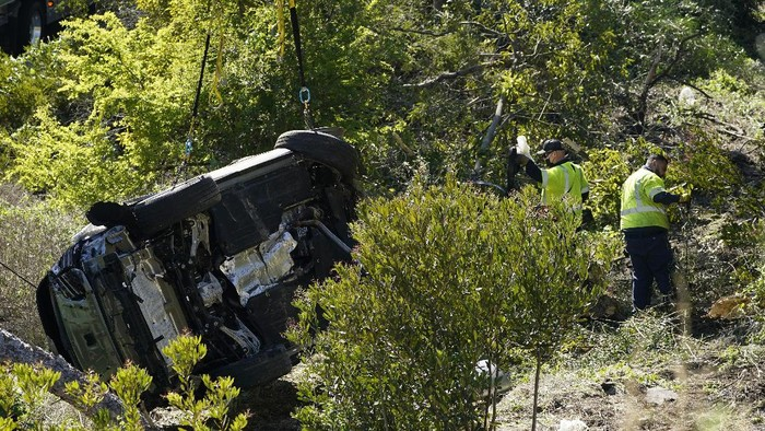Workers collect debris beside a vehicle after a rollover accident involving golfer Tiger Woods Tuesday, Feb. 23, 2021, in Rancho Palos Verdes, Calif., a suburb of Los Angeles. Woods suffered leg injuries in the one-car accident and was undergoing surgery, authorities and his manager said. (AP Photo/Marcio Jose Sanchez)