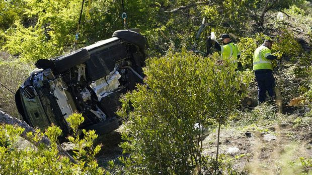 A vehicle is towed away from the site of a crash involving golfer Tiger Woods, Tuesday, Feb. 23, 2021, in the Rancho Palos Verdes suburb of Los Angeles. (AP Photo/Ashley Landis)