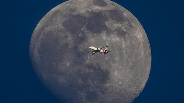 Michael Probst mengabadikan sebuah pesawat terbang dengan latar belakang bulan di langit Frankfurt.