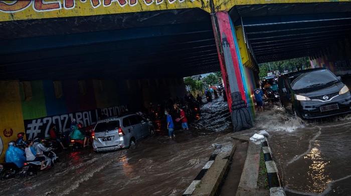 Warga mengarahkan pengendara untuk memanfaatkan trotoar agar sepeda motor mereka tidak mogok saat menembus terowongan dengan tulisan Semarang Hebat!! yang terendam banjir di Jalan Raya Arteri Soekarno-Hatta, Semarang, Jawa Tengah, Kamis (25/2/2021). Banjir yang merendam terowongan jalan raya tersebut dengan ketinggian sekitar 55 cm hingga pukul 18:00 WIB menyebabkan puluhan sepeda motor mogok dan arus lalu lintas terganggu, sementara itu warga setempat membantu mengatur lalu lintas dengan sukarela. ANTARA FOTO/Aji Styawan/foc.