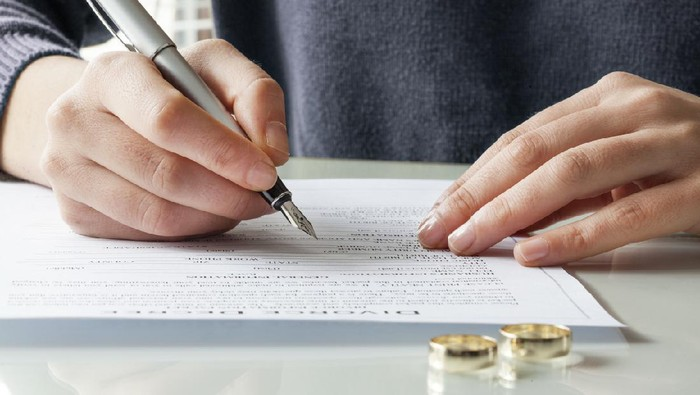 Wife signs divorce decree form with ring