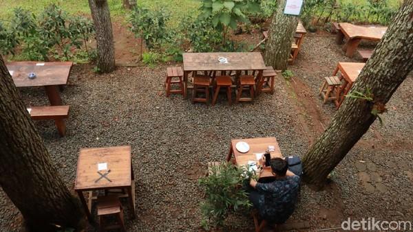 Meja dan kursi kayu berjajar rapih di bawah hamparan pohon pinus. Kamu pun bisa ngopi sambil menikmati suasana teduh hutan pinus yang ada di sini sembari ngobrol dengan teman. (Wisma Putra/detikTravel)