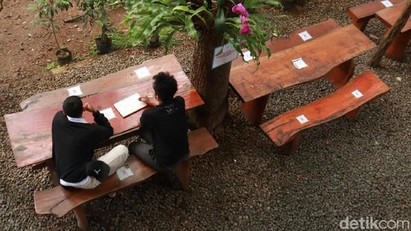 Kalian juga bisa duduk lesehan, dengan lanskap pemandangan hutan pinus. Biasanya, tempat duduk ini kerap digunakan pengunjung yang datang sambil bekerja, membawa laptop dan menyelesaikan pekerjaannya dengan suasana lebih nyaman. (Wisma Putra/detikTravel)