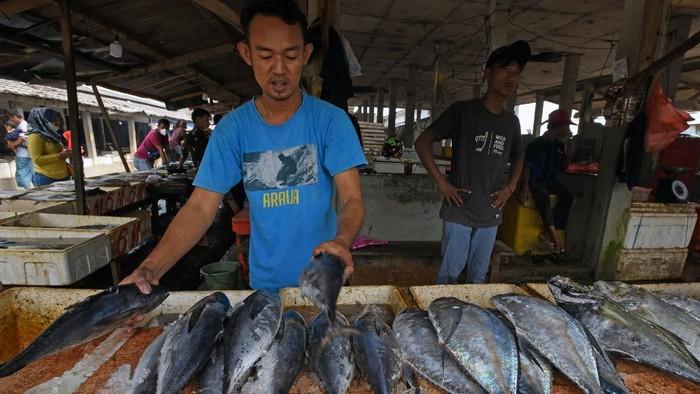 Pedagang ikan melayani pembeli di Pasar Perikanan Nusantara Karangantu, di Kasemen, Serang, Banten, Sabtu (27/2/2021). Menurut Menteri Kelautan dan Perikanan Sakti Wahyu Trenggono angka konsumsi ikan nasional tahun 2020 naik 3,47 persen menjadi 56,39 kg/kapita dibanding tahun 2019 sebesar 54,5 kg/kapita dan ditargetkan akan naik menjadi 62,5 kg/perkapita pada tahun 2024. ANTARA FOTO/Asep Fathulrahman/aww.