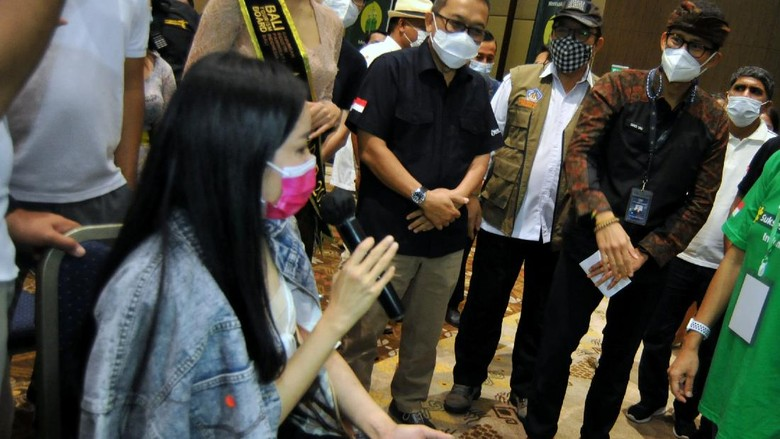 Menteri Pariwisata dan Ekonomi Kreatif (Menparekraf) Sandiaga Salahuddin Uno (kedua kanan) didampingi Wakil Gubernur Bali Tjokorda Oka Artha Ardana Sukawati (ketiga kanan) berbincang dengan pekerja sektor pariwisata yang akan menjalani vaksinasi COVID-19 di Nusa Dua, Badung, Bali, Sabtu (27/2/2021). Vaksinasi COVID-19 kepada pekerja sektor pariwisata yang dimulai di Provinsi Bali tersebut dilakukan untuk mencegah penyebaran COVID-19 sekaligus sebagai salah satu upaya memulihkan sektor pariwisata. ANTARA FOTO/Fikri Yusuf/rwa.