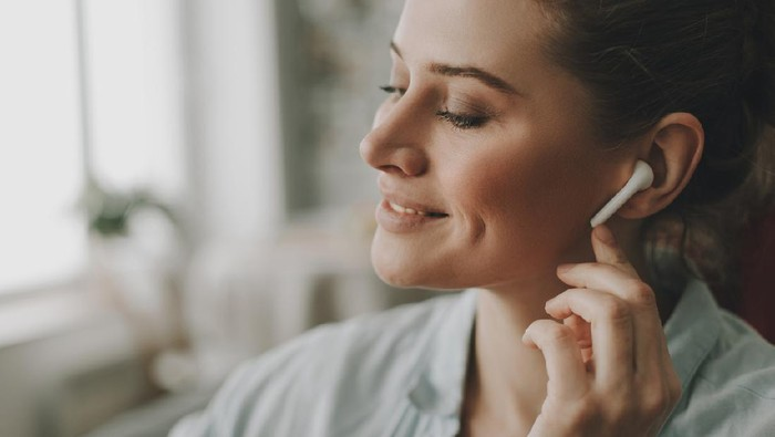 Technology in our life. Close up portrait of young relaxed woman on sofa enjoying of music via wireless earbuds at home