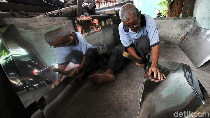Perajin merakit peralatan dapur yang terbuat dari bahan stainless steel dan alumunium di Semanggi, Solo, Jawa Tengah, Senin (1/03). Berbagai jenis kerajinan peralatan dapur antara lain oven, ketel air, kompor oven, penanak nasi dan peralatan lain dijual dari harga 30 ribu hingga 400 ribu rupiah.