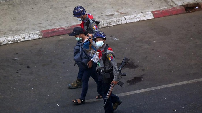 Police arrest Myanmar Now journalist Kay Zon Nwe in Yangon on February 27, 2021, as protesters were taking part in a demonstration against the military coup. (Photo by Ye Aung THU / AFP)